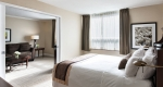 Looking over a freshly made bed into the large living room in an accessible suite at Albert at Bay