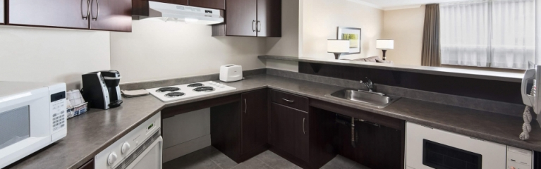 Large kitchen with microwave and stovetop in a superior king one bedroom suite at Albert at Bay