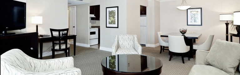 Large living area with two accent chairs and sofa in suite at Albert at Bay