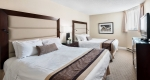 Two double beds with plush bedding in a Superior two bedroom suite at Albert at Bay